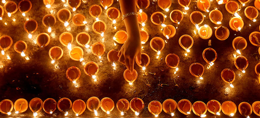 A devotee lights oil lamps at a religious ceremony during the Diwali or Deepavali festival at a Hindu temple in Colombo